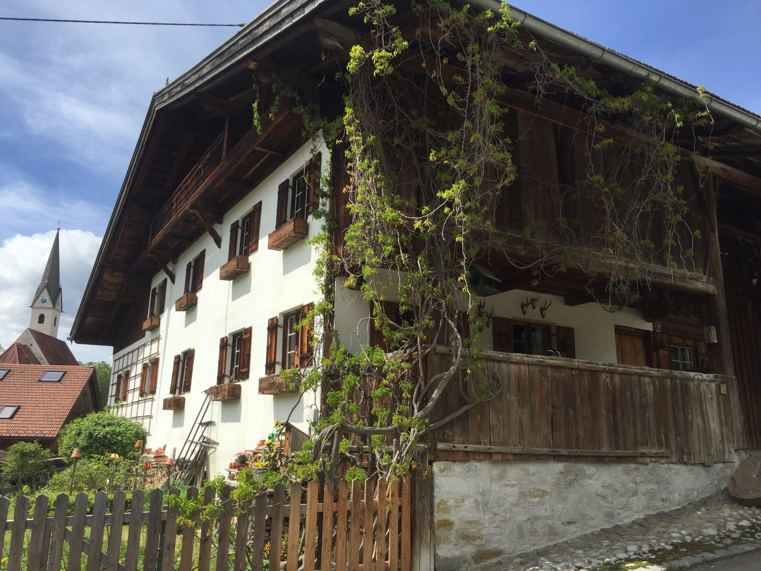 Bauernhaus in Schwangau mit Kirche im Hintergrund